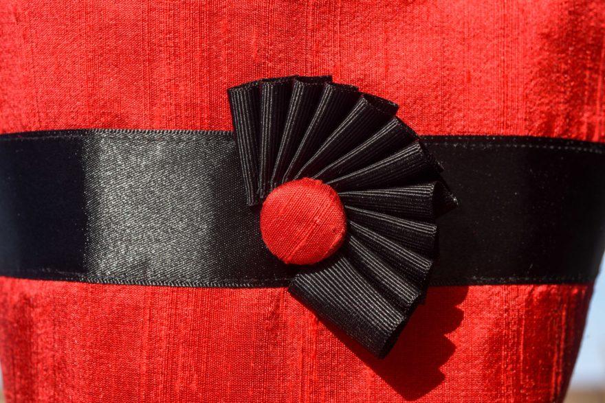 Close up of black cockade on red silk