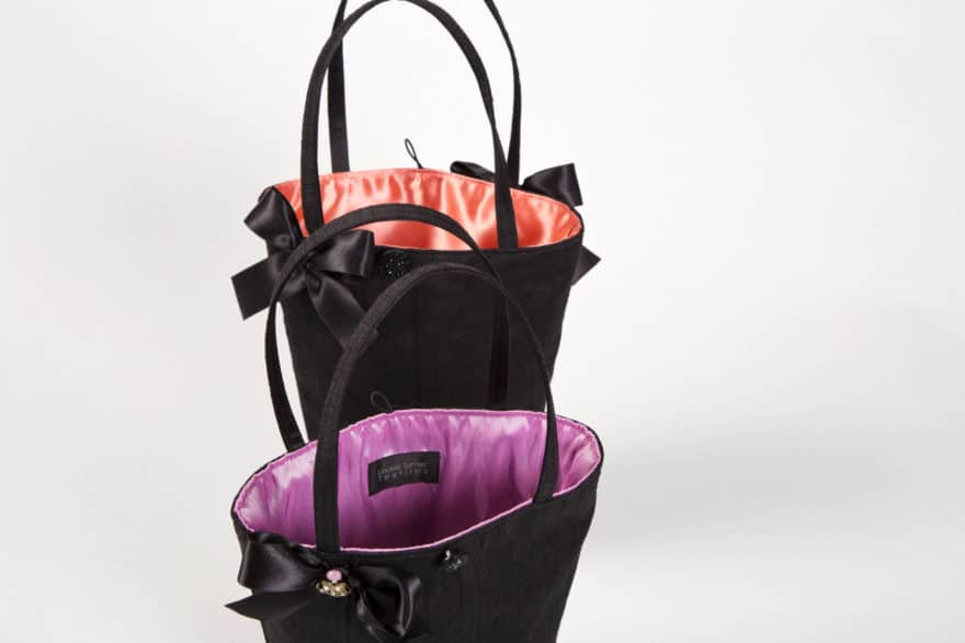 two black handbags with pink and orange linings