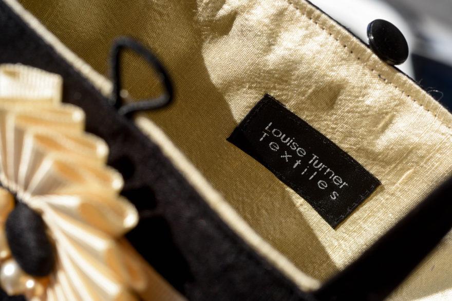Close up of handbag showing brand label inside