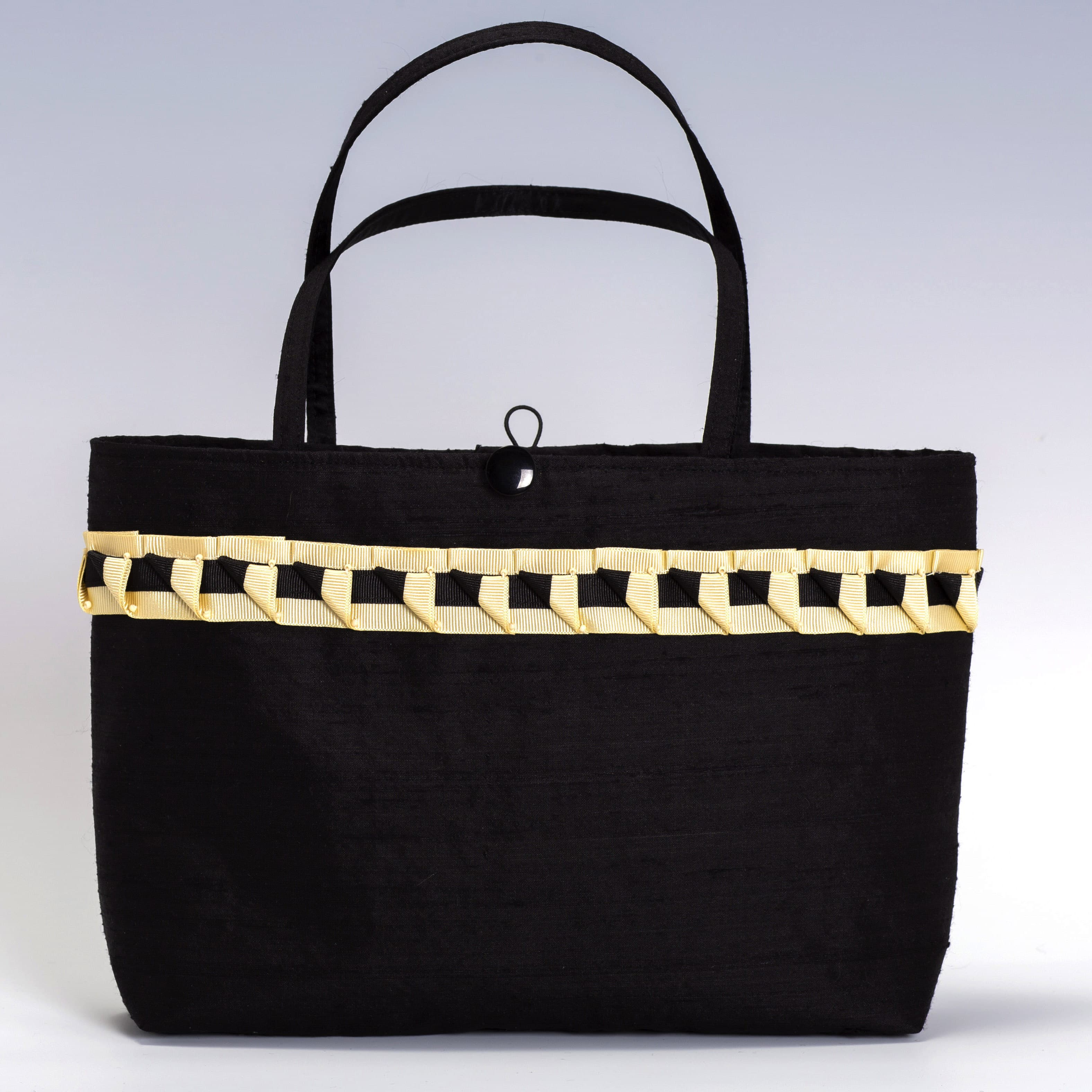 black satin handbag with cream and black trim
