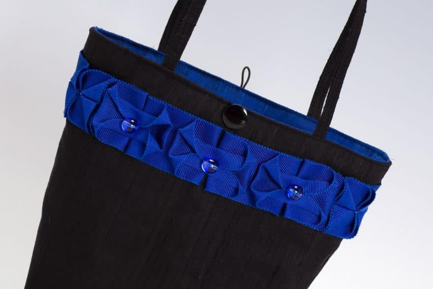 detail of blue ribbon trim on black handbag